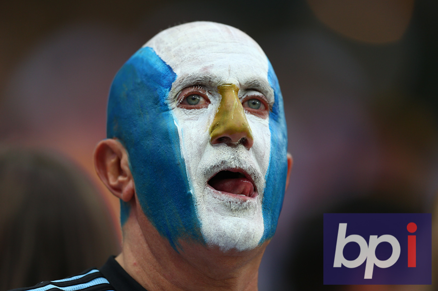An Argentina supporter with a painted face looking pensive before kick off